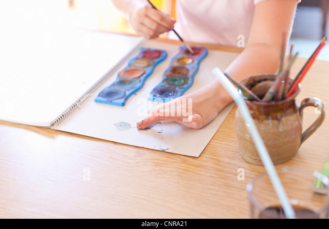 Girl finger-painting with watercolors - Stock-Bilder