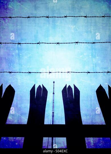 Winter Hill TV mast seen through security fencing - Stock Image