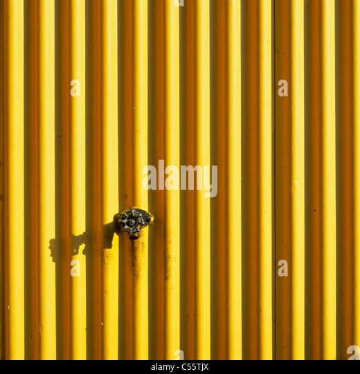 Tap passing through a corrugated iron sheet, Granville Island, Vancouver, British Columbia, Canada - Stock Image