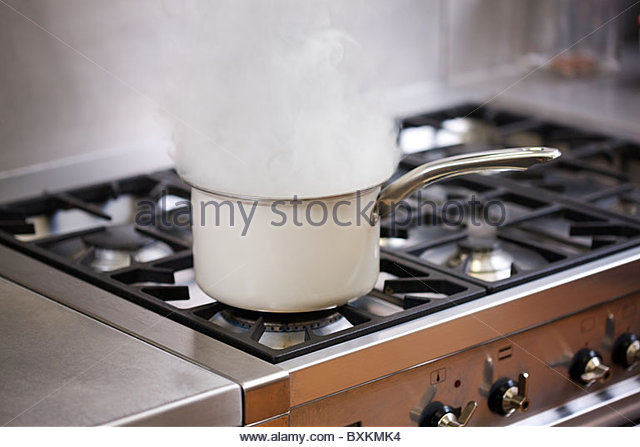 Saucepan boiling on hob with steam - Stock Image