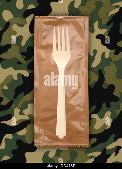 Military food rations or MRE Meals Ready to Eat on a camouflaged background. Packages open with plastic utensils. - Stock-Bilder