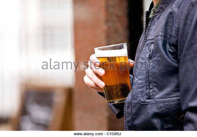 A young man drinking a pint of beer - Stock Image