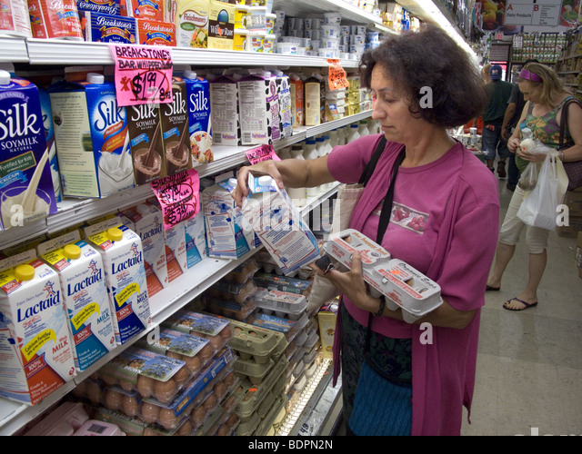 Woman reads food label in the dairy section of a health food market in Brooklyn, New York. MR - Stock Image