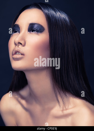 Beauty portrait of an asian woman with sparkling black eyeshadows and black hair - Stock Image