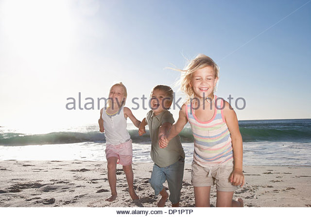 Kids holding hands on beach - Stock Image