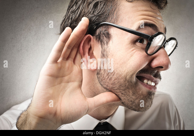 Office worker with glasses can't hear someone - Stock Image