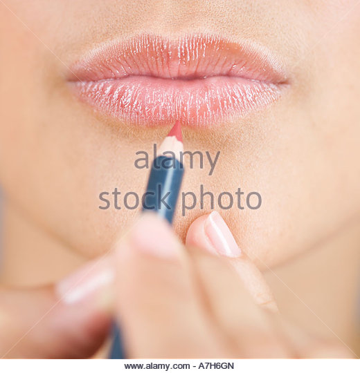 A young woman applying lip liner - Stock Image
