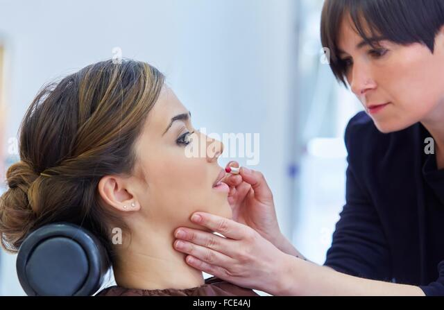 Woman. Makeup artist applying lip liner. Hairdressing salon and Beauty Clinic. - Stock Image
