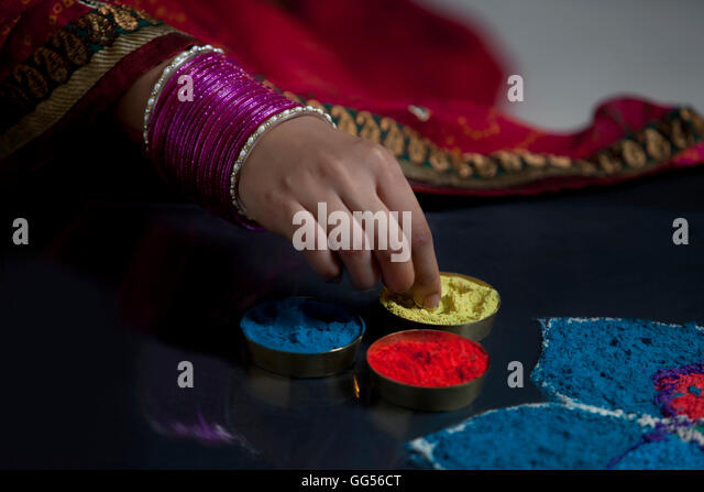 Close-up of woman's hand with bangles making rangoli - Stock-Bilder