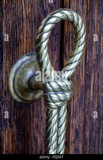 Spain Europe Spanish Madrid Centro Lavapias Calle Argumosa door handle detail bronze rope - Stock Image