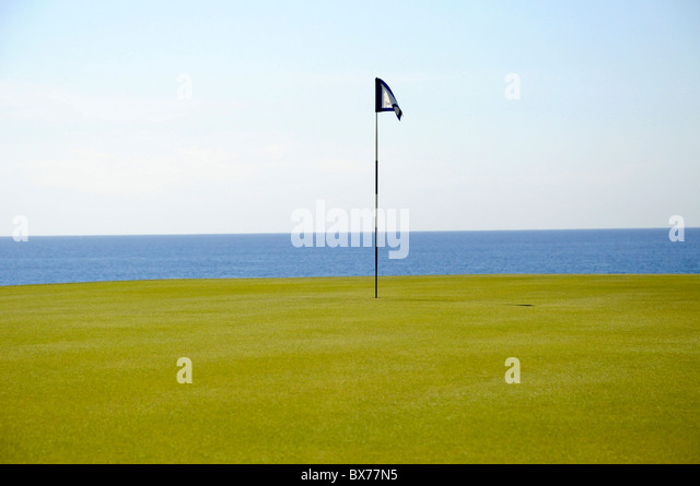 Putting green and flag pole on 14th hole at Puerto Los Cabos Golf Club in San Jose del Cabo, Mexico - Stock Image