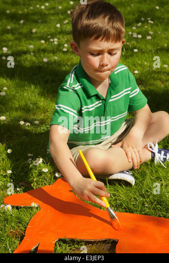 Boy Painting Cardboard Cut Out in Garden - Stock Image