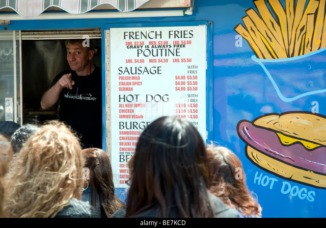 The owner of Toronto's famous Mr. Tasty Fries - also known as 'The Blue Chip Truck' - taking an orders - Stock Image