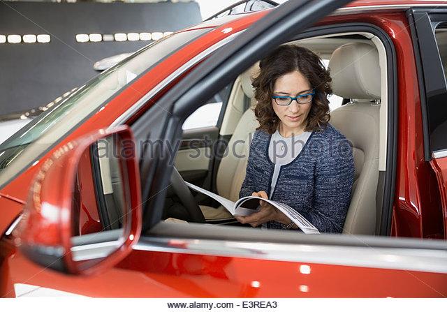 Woman looking at brochure inside car at dealership - Stock Image