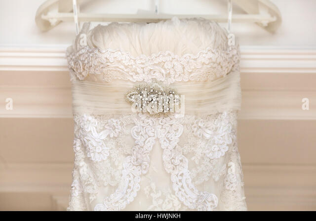 A close up of a wedding dress with a large silk bow - Stock Image