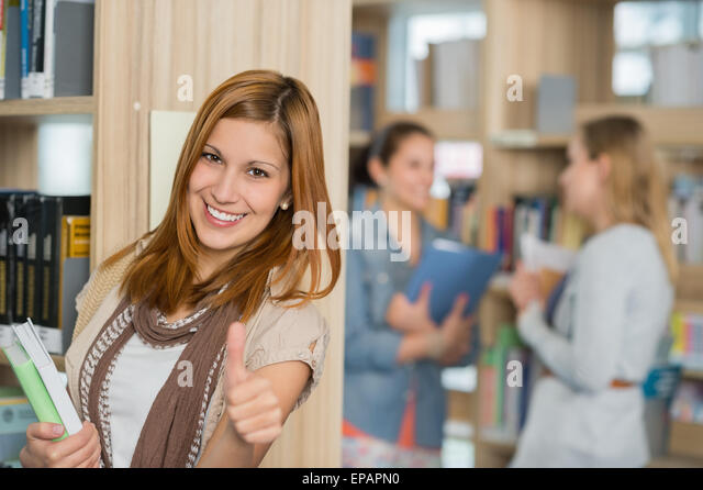 Student showing thumb up in library - Stock Image