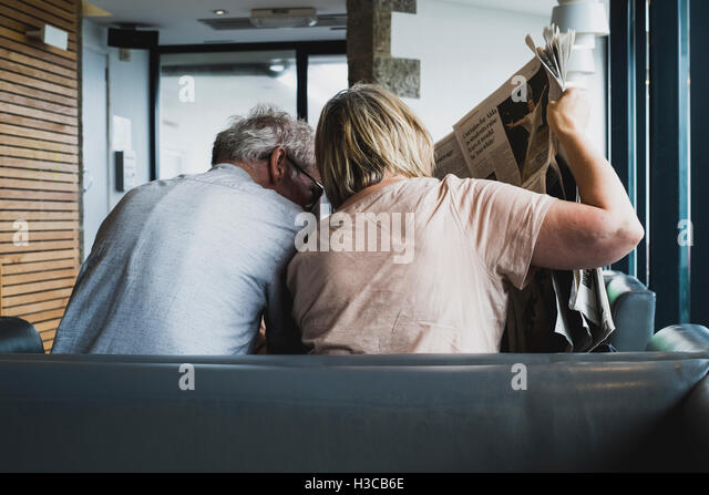 A couple reading a broadsheet newspaper at Gylly Beach Cafe, Gyllyngvase beach, Falmouth, Cornwall - Stock Image