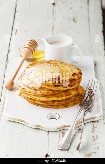 Stack of Small pancakes with butter and honey - Stock Image
