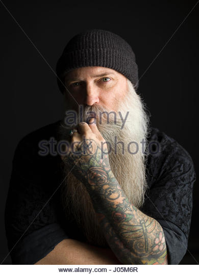 Portrait serious tattooed hipster man with long gray beard against black background - Stock Image