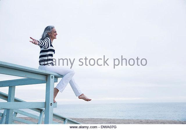 Mature woman sitting on seaview balcony at coast, Los Angeles, California, USA - Stock Image