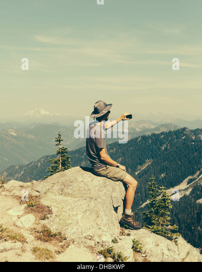 A hiker on mountain summit holding smart phone at top Surprise Mountain in Alpine Lakes Wilderness in Mount Baker - Stock Image