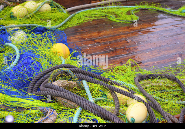 fishermen professional tackle net on boat wooden wet deck - Stock Image