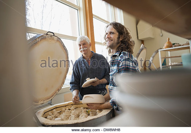 Pottery technicians standing by kiln - Stock Image