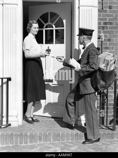 1930s POSTMAN GIVING A LETTER TO A WOMAN IN THE DOORWAY OF A COLONIAL BRICK HOME - Stock Image