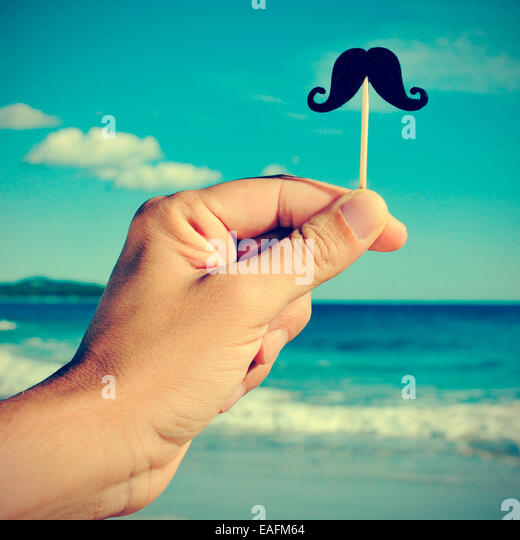 a man hand holding a fake moustache in a stick in his hand on the beach, with a filter effect - Stock Image