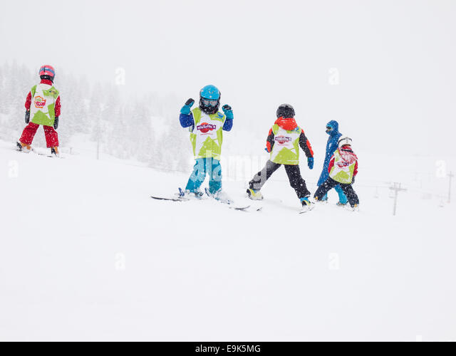 young children aged five years wearing helmets and goggles learning to ski in a group lesson with instructor in - Stock Image