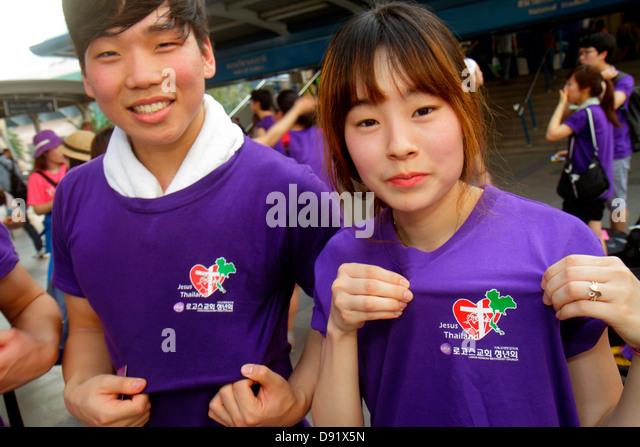 Thailand Bangkok Pathum Wan Rama 1 Road Asian teen boy girl Jesus Thailand Christian religious t-shirt - Stock Image