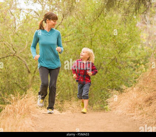 Mother and son running in forest - Stock Image