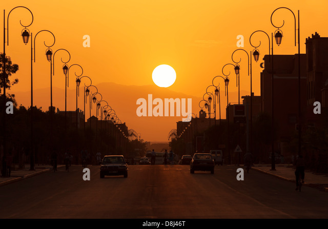 Silhouette city scene with street and street lamps against sunset. - Stock Image
