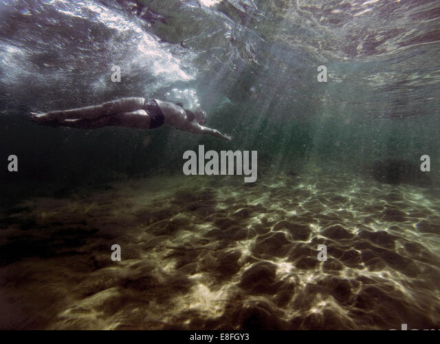 Woman swimming underwater in sea - Stock Image