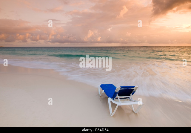 Caribbean Dominican Republic Lounge chair on beach at sunrise in front of all inclusive resort - Stock-Bilder