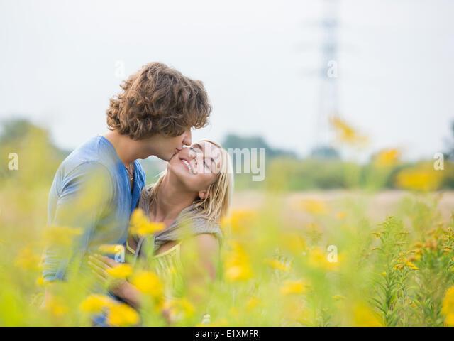 Romantic man kissing woman in field - Stock-Bilder