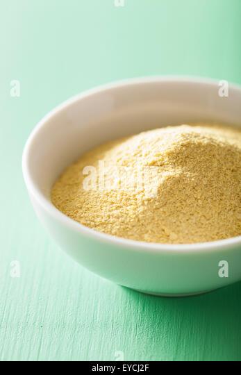 vegan nutritional yeast flakes in bowl - Stock Image