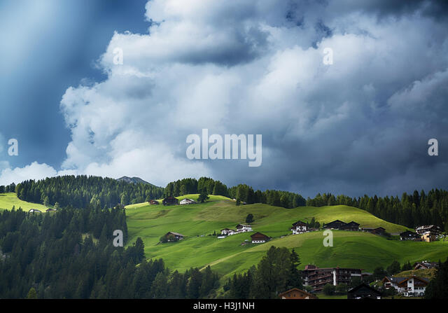 Thunderstorm formation over the green hills and forest of the Dolomites, Trentino-Alto Adige - Italy - Stock Image