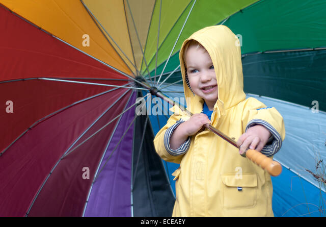 Boy in a rain coat holding multi-colored umbrella - Stock Image