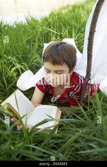 Girl reading book in tall grass - Stock Image