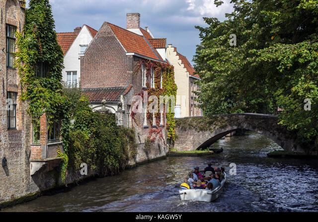 Tourist boat on the canals of the Begijnhof area of the city of Bruges in Belgium. The historic city centre is a - Stock Image
