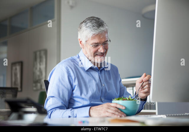 Businessman sitting at desk, eating salad - Stock Image