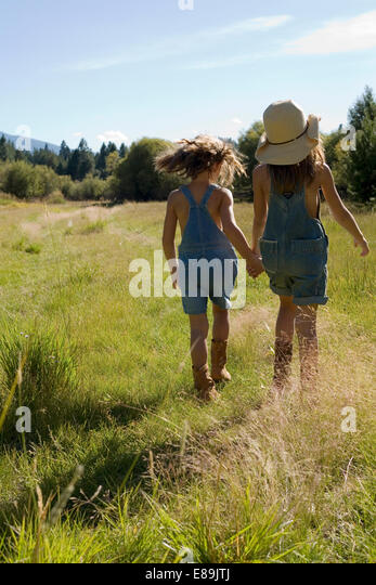 Sisters in overalls walking in field - Stock-Bilder