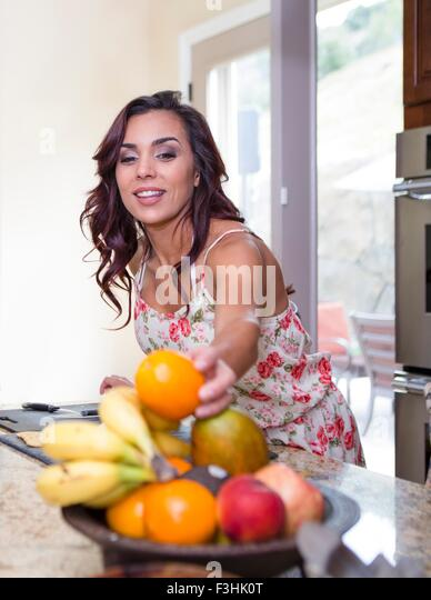 Mid adult woman picking up orange from fruit bowl - Stock Image