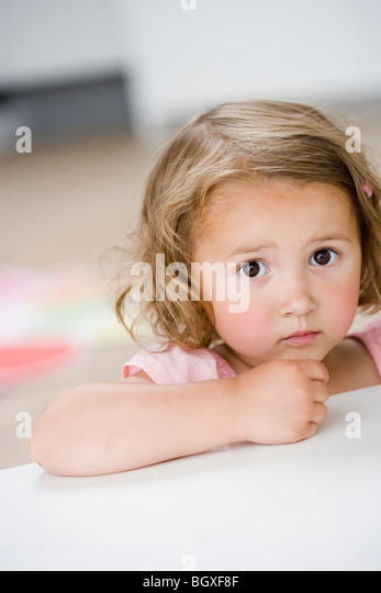 young girl frowning at viewer - Stock Image