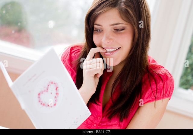 woman looking at a Valentine s day card - Stock Image