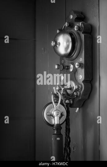 Old antique telephone hanging on wall. Vintage technology. Classic communication equipment. - Stock-Bilder