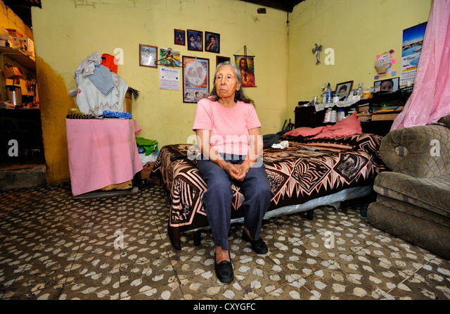 Old woman sitting in her humble apartment, El Esfuerzo slum, Guatemala City, Guatemala, Central America - Stock Image