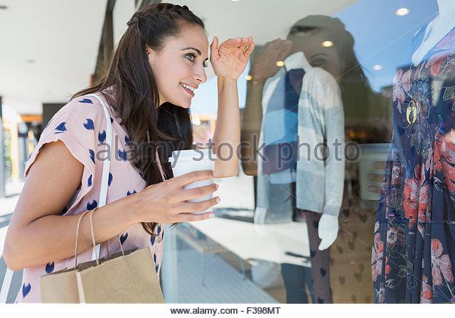Woman with coffee peering clothing shop window display - Stock Image