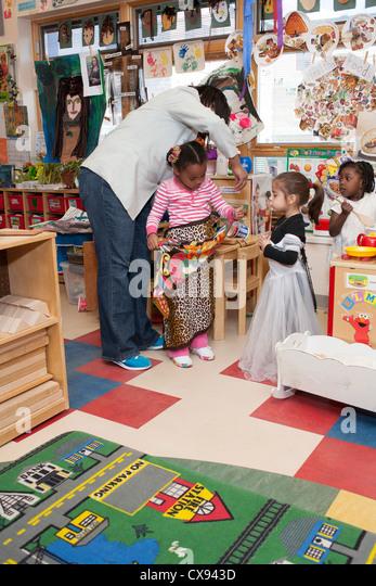 Female African-American preschool teacher helping girl students play dress up - Stock Image